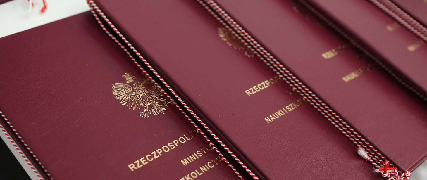 Dyplomy w brązowych okładkach